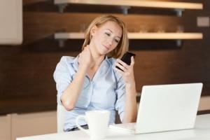 Frau an Laptop mit Handy über mobiles Internet