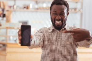 Mann freut sich über neues Smartphone mit Vertrag